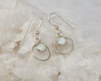 Silver opal hoop earrings on white rock