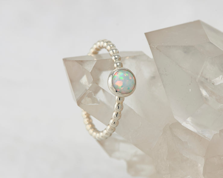 Silver beaded ring dangling from crystal rock