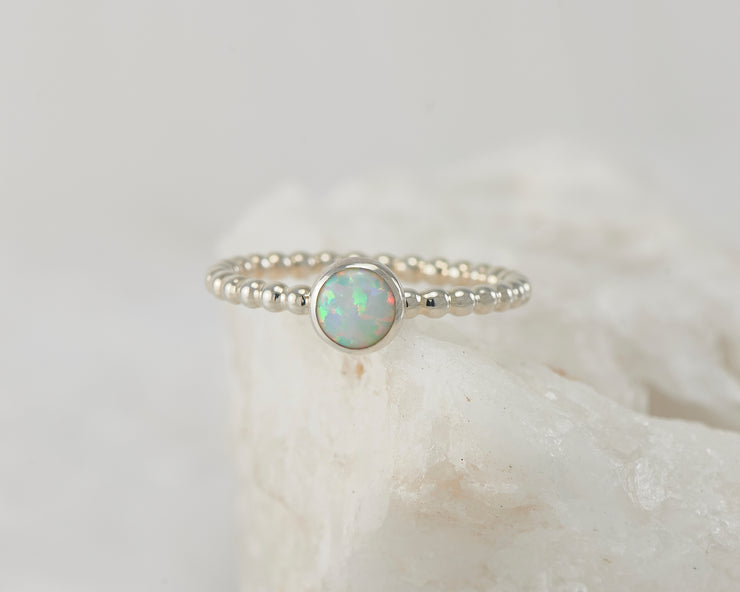 Silver opal beaded ring on white rock