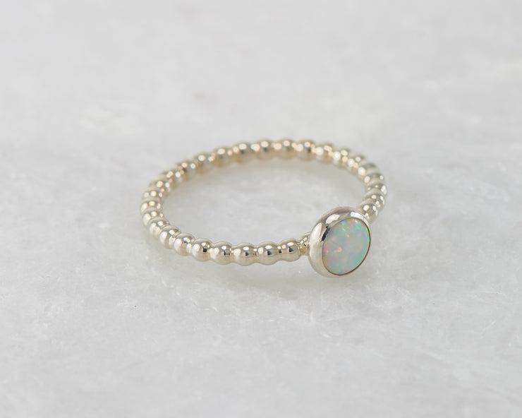 beaded opal ring on white marble