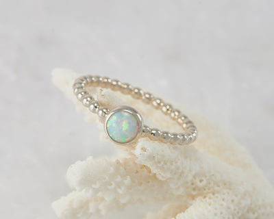 Silver opal ring on coral