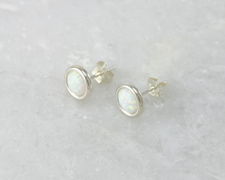 Silver stud opal earrings on white marble