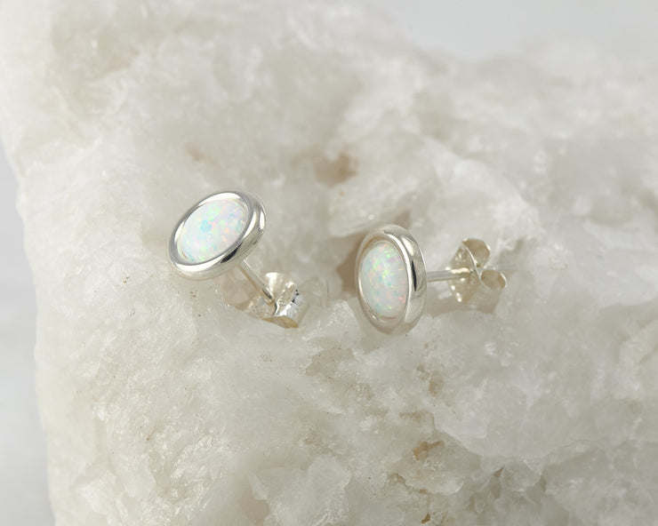 Silver opal stud earrings on white rock