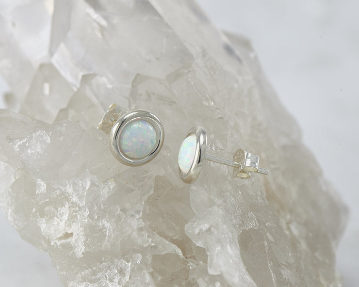 Silver opal earrings on crystal rock
