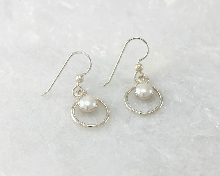 Silver polished pearl hoop earrings on white marble