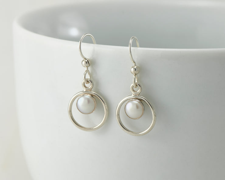 Silver pearl hoop earrings on white cup
