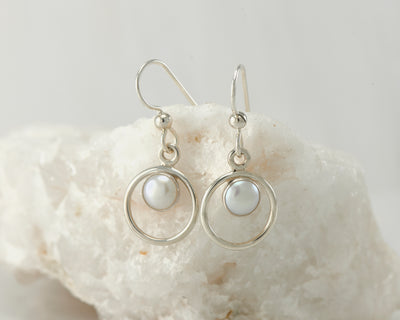 Silver pearl hoop earrings on white rock