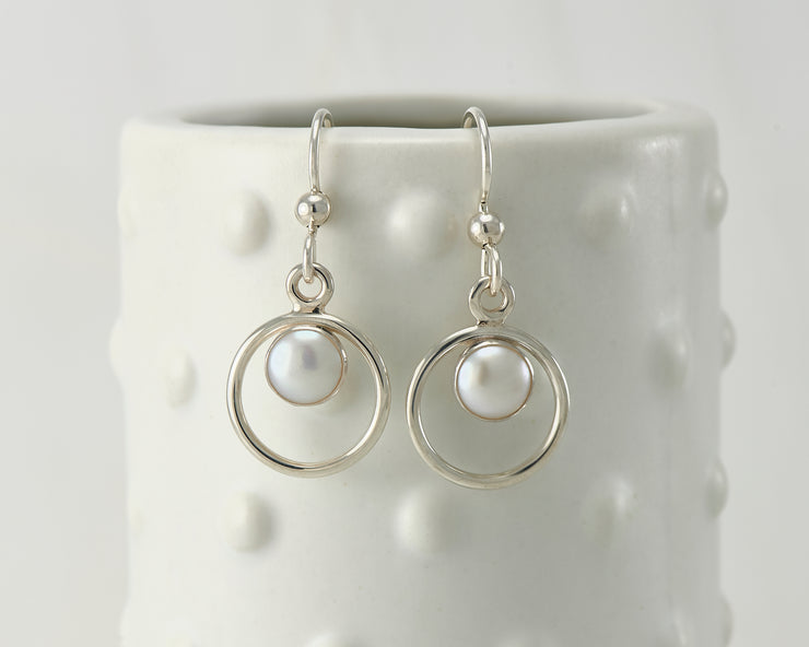 Silver polished pearl hoop earrings on dotted vase