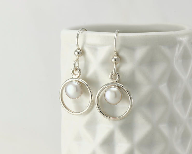 Silver pearl hoop earrings on geometric vase