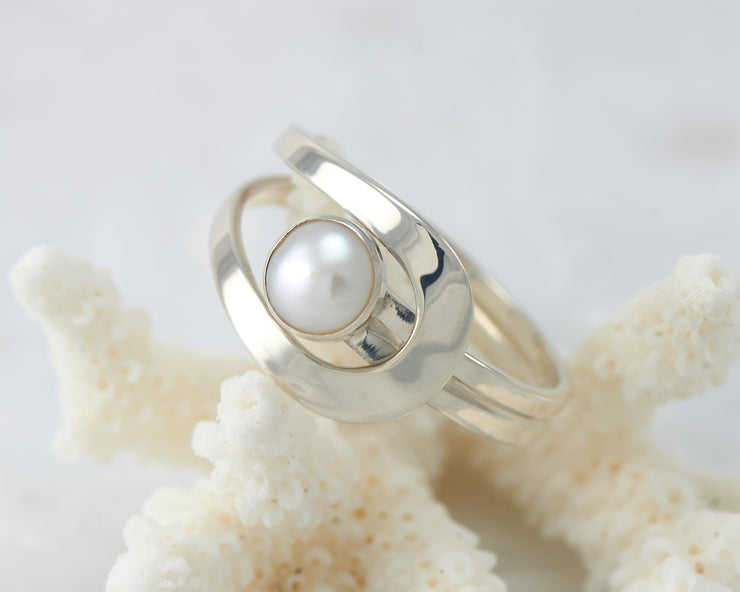 Silver pearl ring on coral