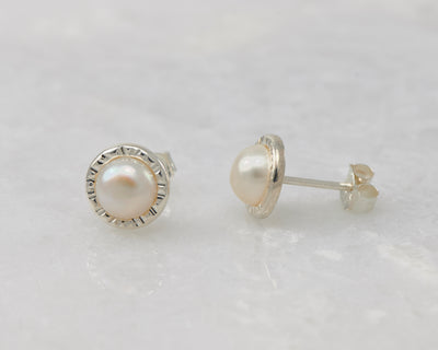 silver pearl stud earrings on white marble
