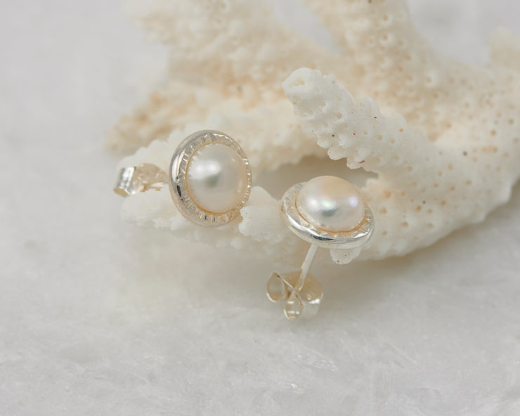 silver pearl stud earrings on coral