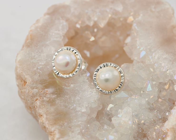 silver pearl stud earrings on quartz
