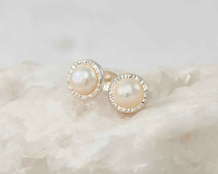 Silver dangle pearl stud earrings on white rock