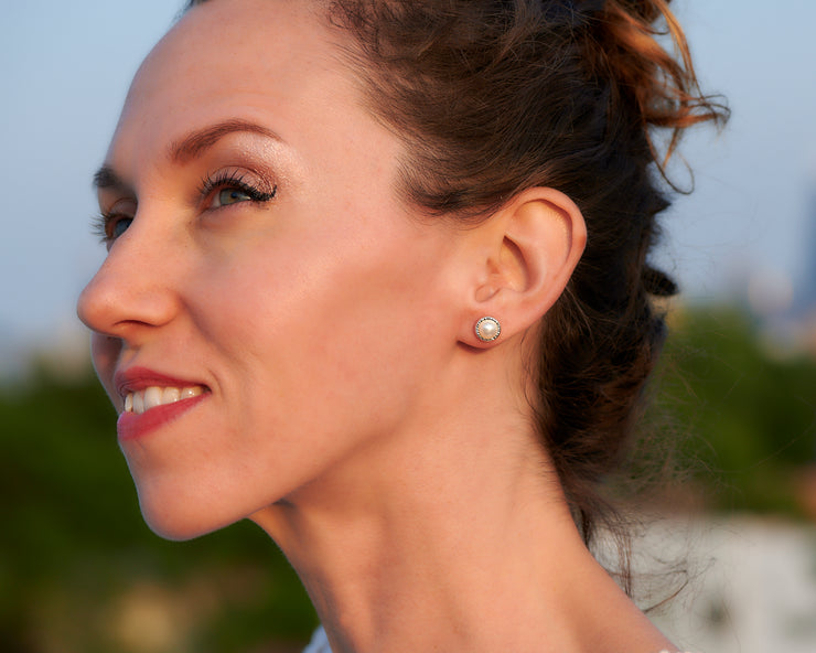 woman wearing silver pearl stud earrings