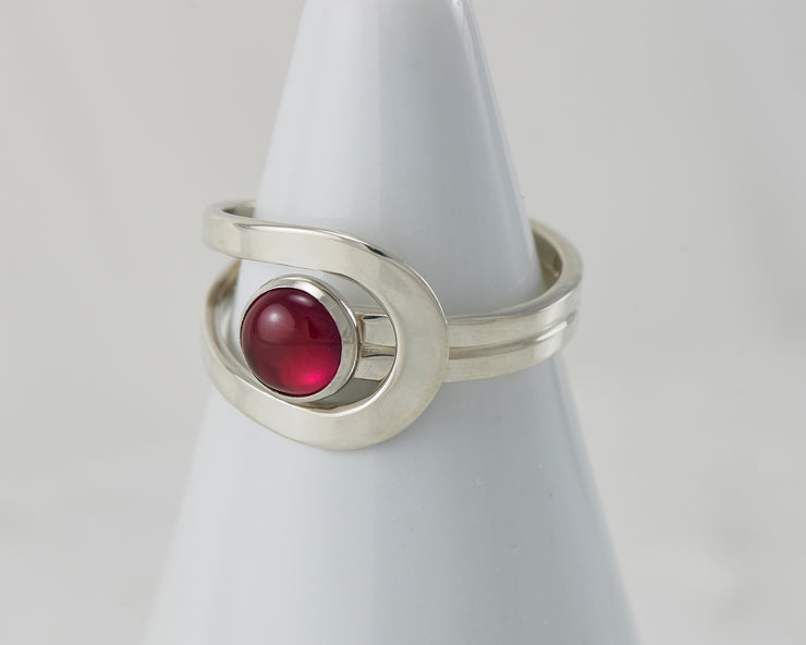 White ring holder with ruby Silver ring