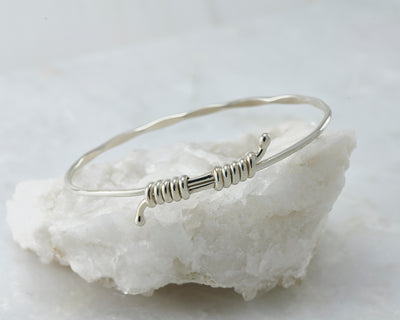 adjustable Silver bangle bracelet on white rock