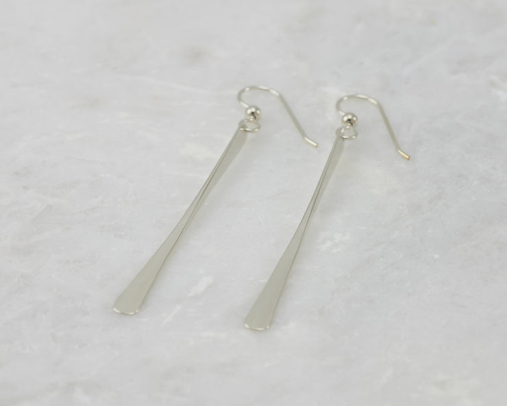 silver bar earrings on white marble
