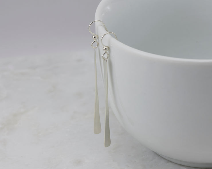 silver bar earrings on white cup