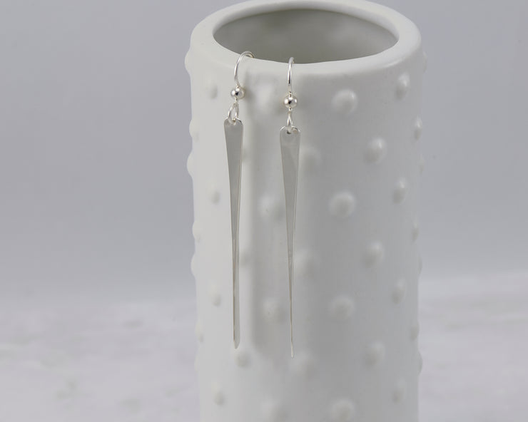 silver bar earrings on dotted vase