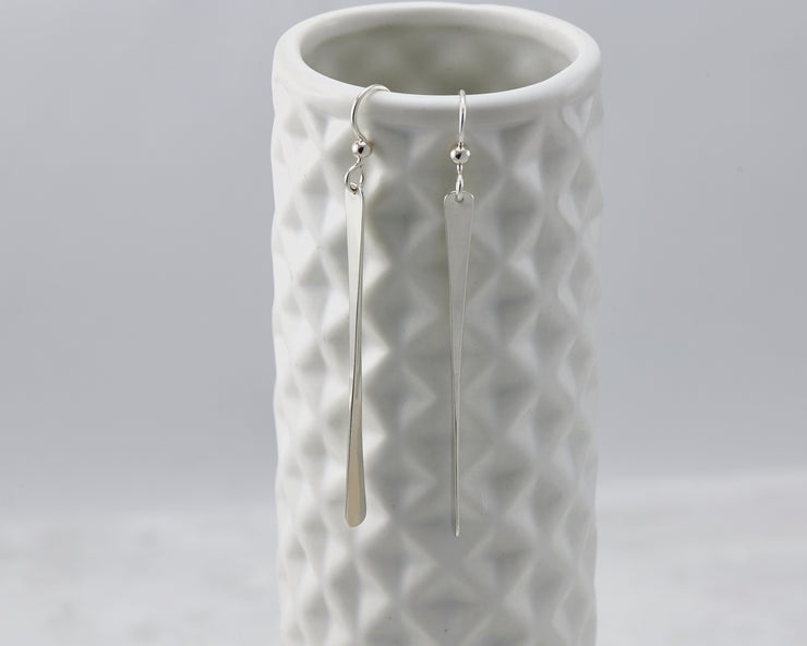 silver bar earrings on geometric vase