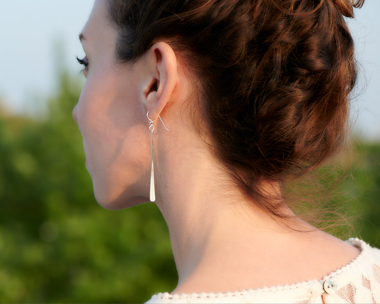 woman facing away wearing silver bar earrings