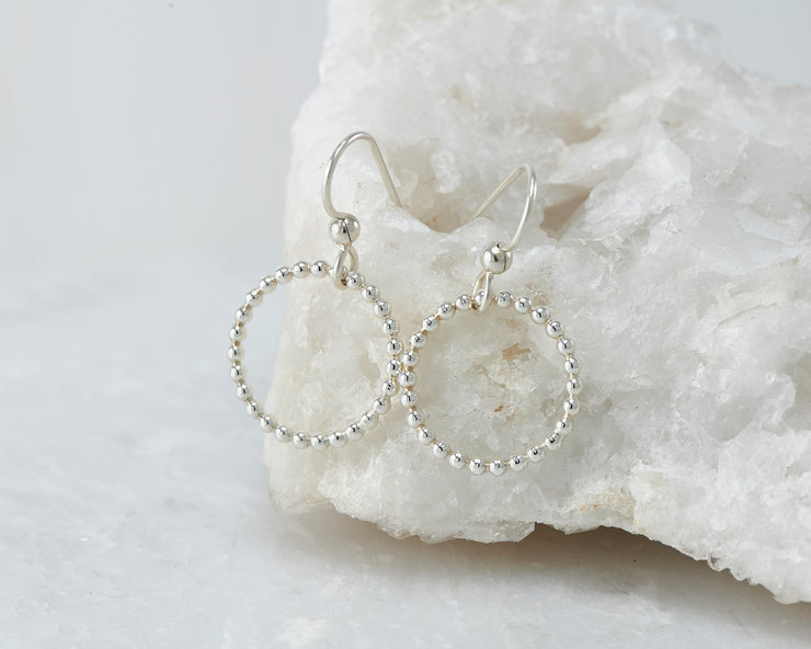 Silver beaded circle hoop hoop earrings on white rock