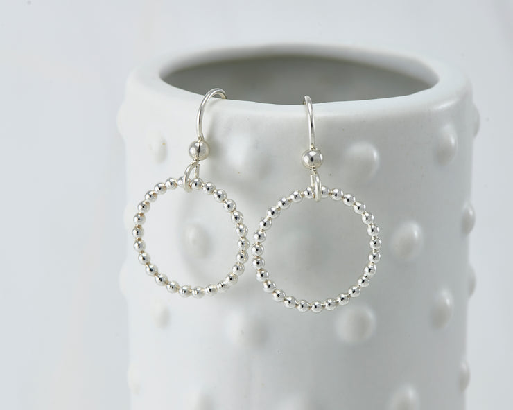 Silver polished beaded circle hoop earrings on dotted vase