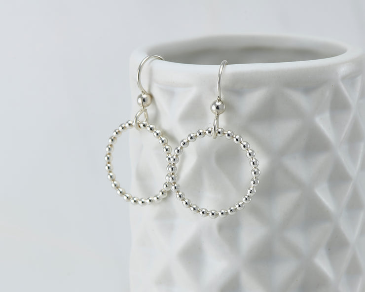 Silver beaded circle hoop earrings on geometric vase