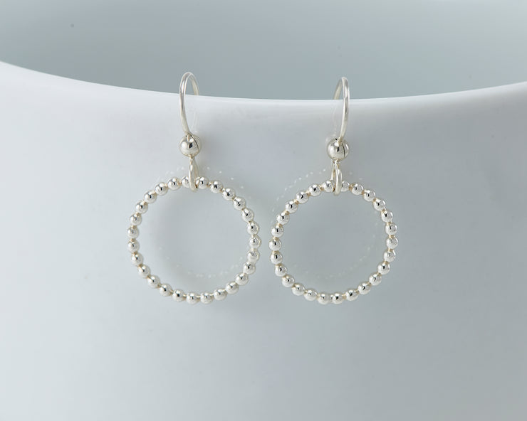 Silver beaded circle hoop earrings on white cup