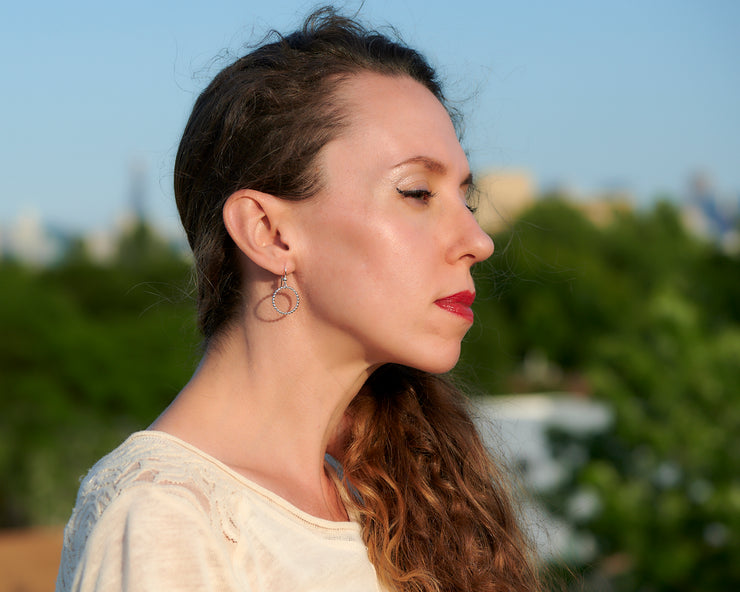 Woman wearing silver hoop beaded circle hoop earrings