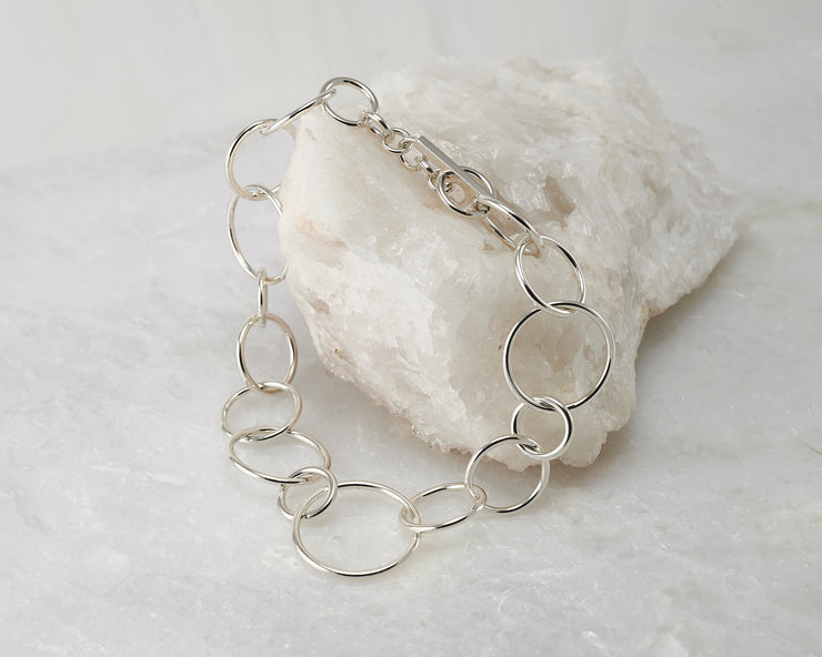 Silver chain link Bracelet closed on white rock