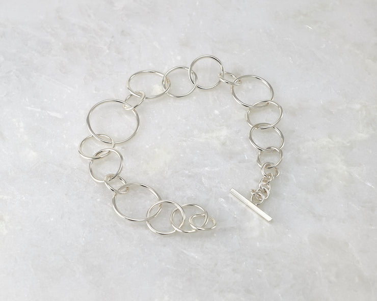 latch style chain link silver bracelet open on marble