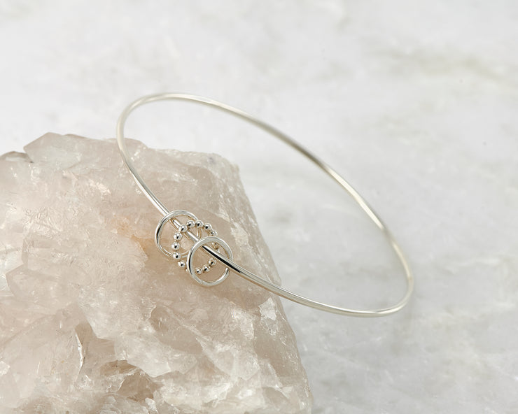 Silver charms bangle on white rock