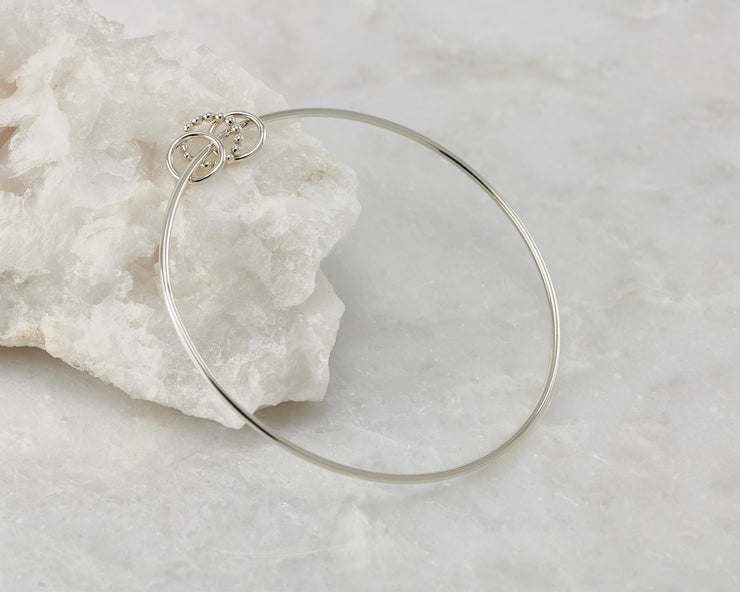 bangle silver charms bracelet open on white rock