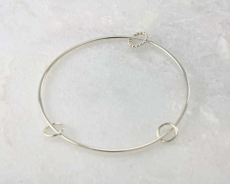 bangle style charms silver bracelet on marble