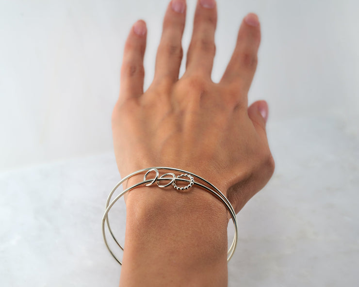 woman wearing silver charms bangle bracelet