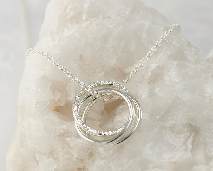 Silver interlocking unity necklace on white rock