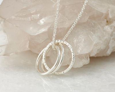 Silver interlocking unity necklace on crystal rock