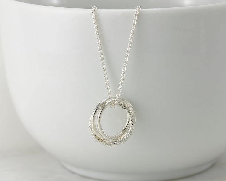 Silver interlocking unity necklace on white cup
