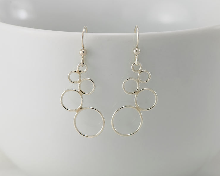Silver circles chandelier earrings on white cup