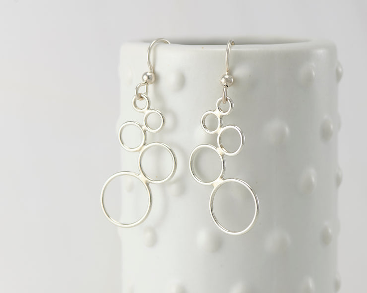 Silver polished circles chandelier earrings on dotted vase