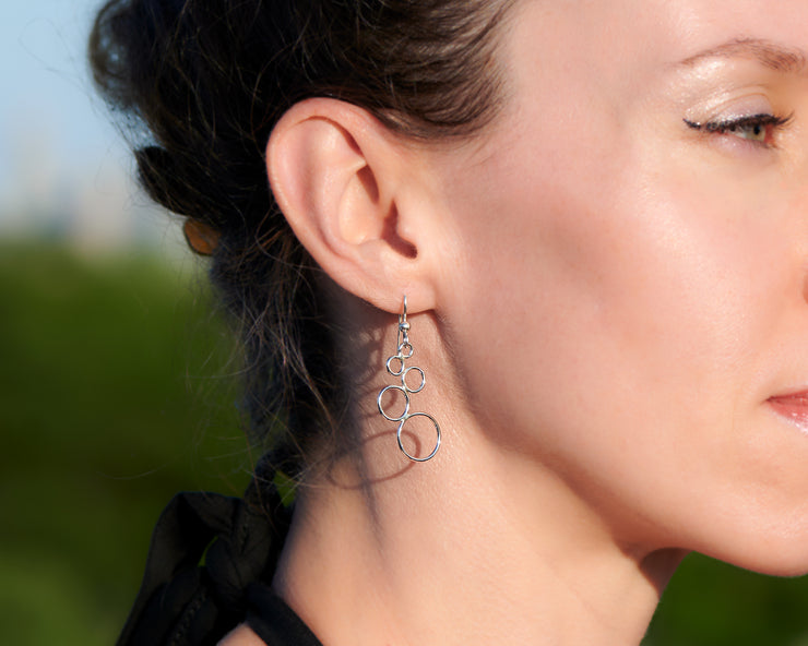 close up of woman wearing silver circles chandelier earrings