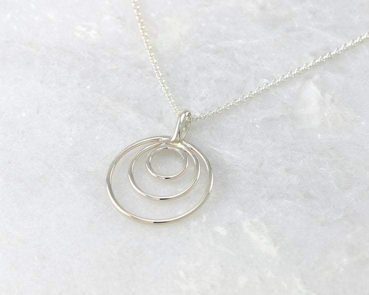 silver circles necklace on white marble