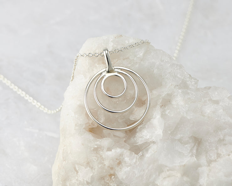 silver circles necklace on white rock