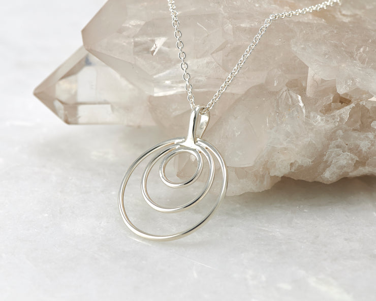 Silver circles necklace on crystal rock