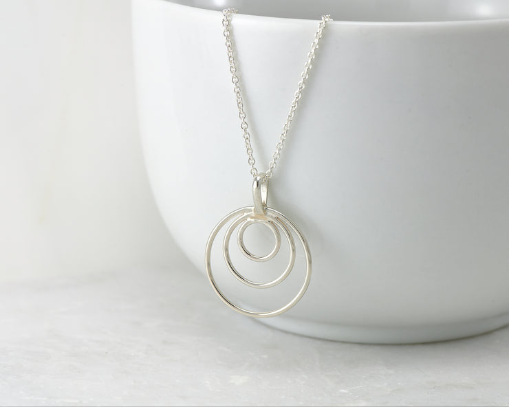 silver circles necklace hanging from white cup