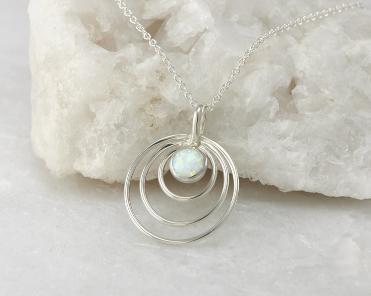 Silver opal circles necklace on white rock