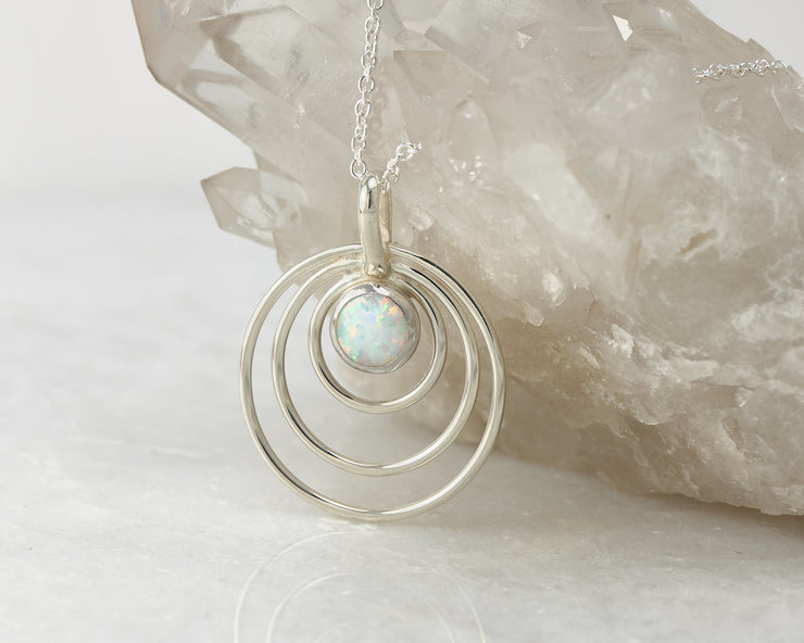 Silver opal circles necklace on crystal rock