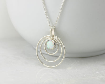 Silver opal circles necklace on white cup